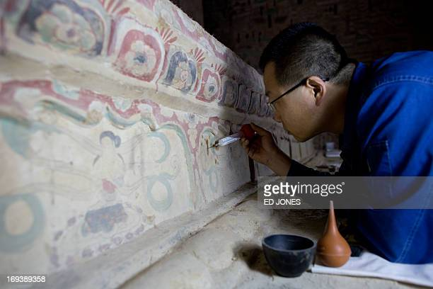 To go with AFP story ChinaheritagetechnologyartFEATURE by Sebastien Blanc In a photo taken on May 13 2013 a technician restores one of the Mogao...