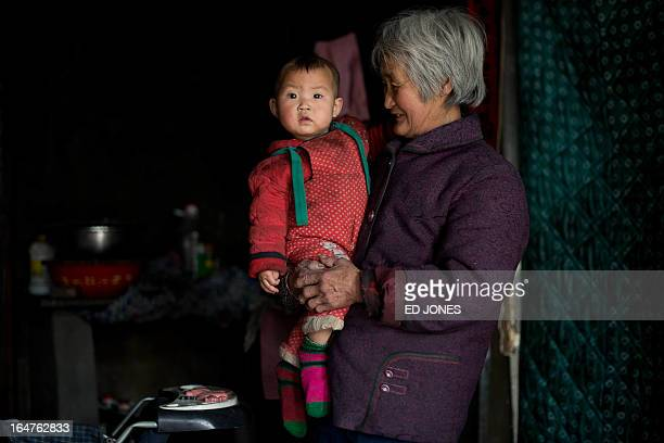 To go with AFP story 'ChinapopulationsocialFOCUS' by Carol Huang A photo taken on March 21 2013 shows a woman holding her granddaughter in their home...