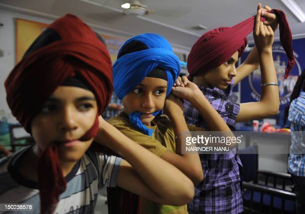 To go with AFP story IndiaculturereligionSikhturbanFEATURE by Ammu Kannampilly This picture taken on July 3 2012 shows young Indian Sikh men tying...