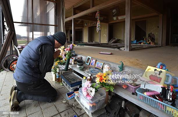 To go with AFP story JapanNuclearDisasterTsunamiAnniversary FOCUS by Harumi Ozawa In a picture taken on March 8 a volunteer member prays at an altar...