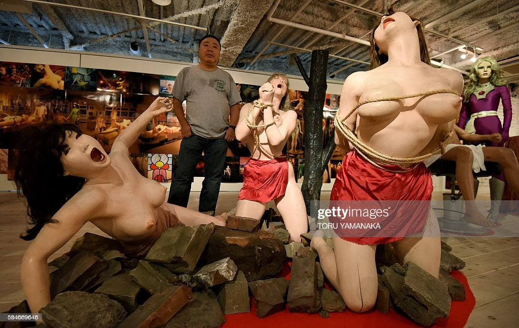 To go with AFP story 'Japan-sex-culture-exhibition' by Harumi OZAWA Photographer Kyoichi Tsuzuki stands beside life-like female dolls tied up in bondage ropes and screaming in agony at the Erotopia Japan exhibition in Tokyo on July 28, 2016. The sex exhibition smack in the middle in one of Tokyo's hippest areas is shining a nostalgic light on Japanese erotica -- a culture the curator believes is dying out. / AFP / TORU