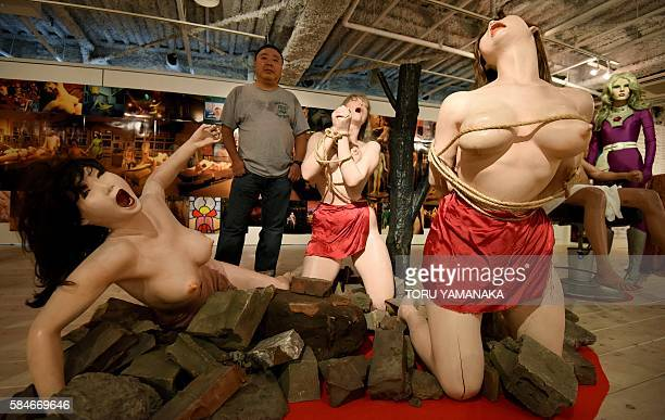To go with AFP story 'Japansexcultureexhibition' by Harumi OZAWA Photographer Kyoichi Tsuzuki stands beside lifelike female dolls tied up in bondage...