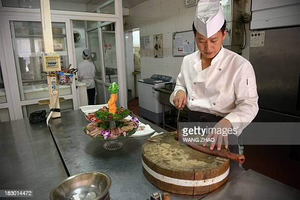 To go with AFP Story LifestylefoodChinaIndonesiaPakistansexFEATURE by Neil Connor This picture taken on September 12 2013 shows a cook preparing a...