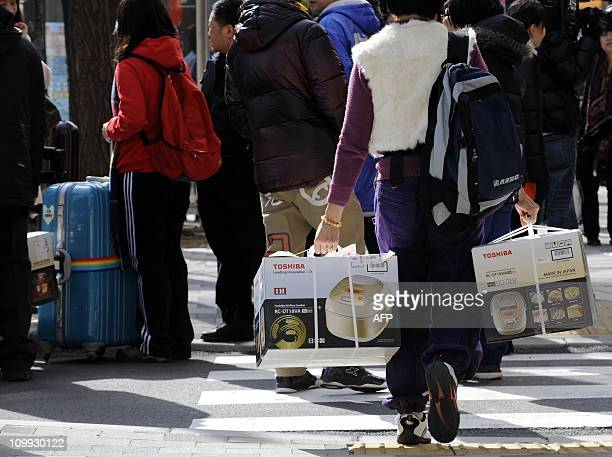 To go with AFP story 'LifestyletourismJapanChinaeconomyFEATURE' by Harumi OzawaPhoto taken on February 10 2011 shows a Chinese tourist carrying rice...