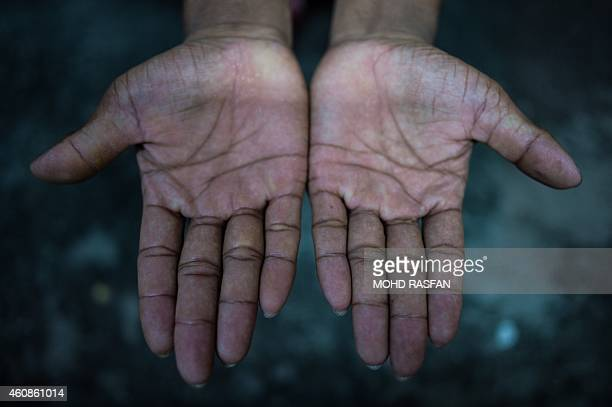 To go with AFP story MalaysiaeconomyrightslabourelectronicsFEATURE by Satish Cheney In this photo taken on November 27 2014 a Nepalese worker using...