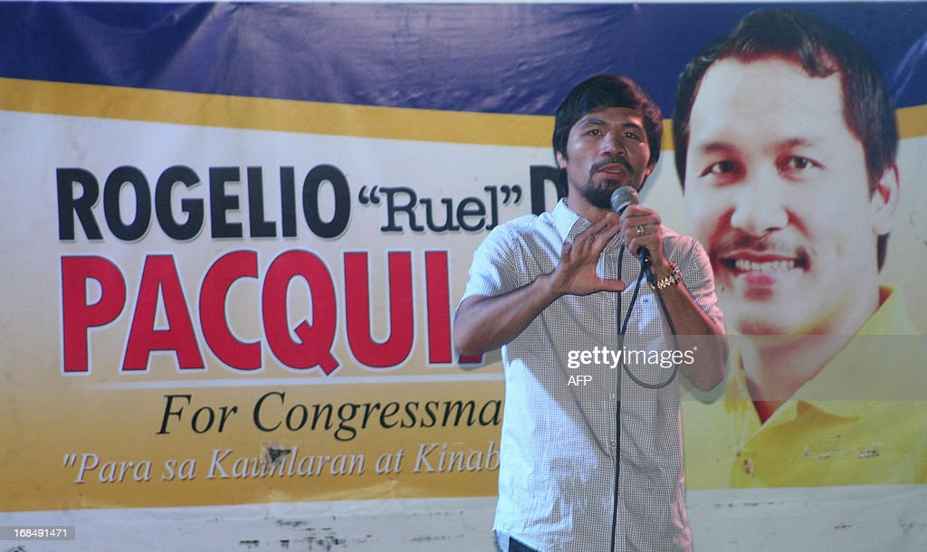 To Go with AFP story 'Philippines-Vote-Dynasty-FOCUS' by Karl Malakunas In this photo taken on April 28, 2013 shows boxing champion Manny Pacquiao gesturing as he speaks next to a poster of his brother Rogelio Pacquiao, who's running for congress, during a political campaign in General Santos City in southern island of Mindanao. Manny Pacquiao, a former street kid who used his hero status and wealth from sports to beat an entrenched dynastic ruler of a southern province for a seat in the nation's lower house in 2010. For next week's elections, Pacquiao has deployed his wife, Jinkee, a former shopping mall saleswoman with no political experience, to run as vice governor of Sarangani province. One of Pacquiao's brothers is also aiming to join him in Congress representing another southern province. AFP PHOTO/Paul Bernaldez
