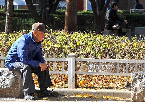 To go with AFP story SKoreapoliticsvotesociety Focus by Jung HaWon South Korean men relax at a downtown park in Seoul on November 1 2012 South...