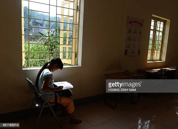 To go with AFP story VietnamChinawomentraffickingsocialFEATURE by CAT This picture taken on May 9 2014 shows H'mong ethnic girl Kiab reading her...