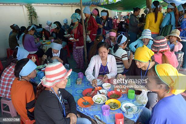 To go with Cambodia-textile-social-economy,FEATURE by Suy Se This photo taken on May 8, 2014 shows Cambodian garment workers having lunch at a shop...
