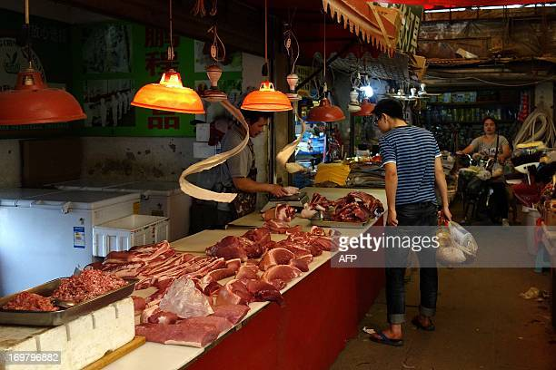 To go with ChinaeconomyforeignmergerFOCUS by Kelly Olsen In this picture taken on June 1 2013 a man browses meat at a shop selling pork in Beijing A...