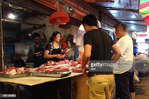 To go with ChinaeconomyforeignmergerFOCUS by Kelly Olsen In this picture taken on June 1 2013 a butcher prepares to process meat for customers at a...