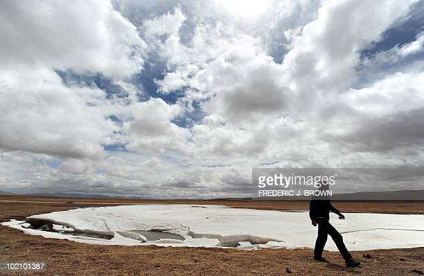 To go with China-Environment-Climate-Rivers by Robert Saiget A man walks past ice-melt in the source region of China's Yellow River outside of Maduo...