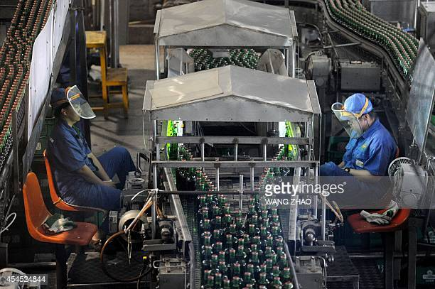 To go with ChinaGermanyJapaneconomydrinkFOCUS by Kelly OLSEN This picture taken on July 24 2014 shows Chinese workers minding a filling workshop at...
