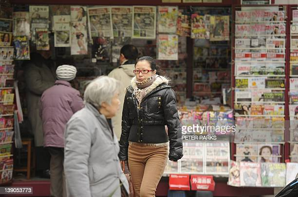 To go with ChinalanguageeducationdialectShanghai story by Bill Savadove In this picture taken on February 8 2012 ppedestrians walk past a news stand...