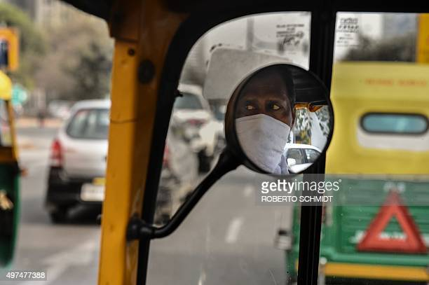 To go with ClimatewarmingUNCOP21IndiaFOCUS by Trudy Harris In this photo taken on February 18 auto rickshaw driver Asok Kumar uses a hankerchief to...