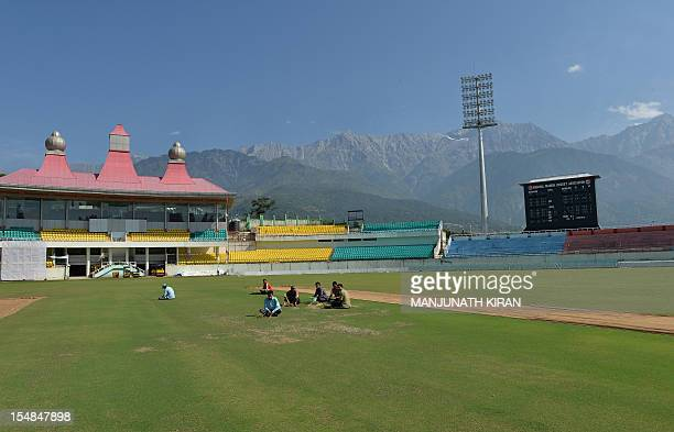 To go with 'CricketINDENGIndiaBritaintourism' by Ben Sheppard In a picture taken on September 26 workers prepare the turf at the cricket stadium of...