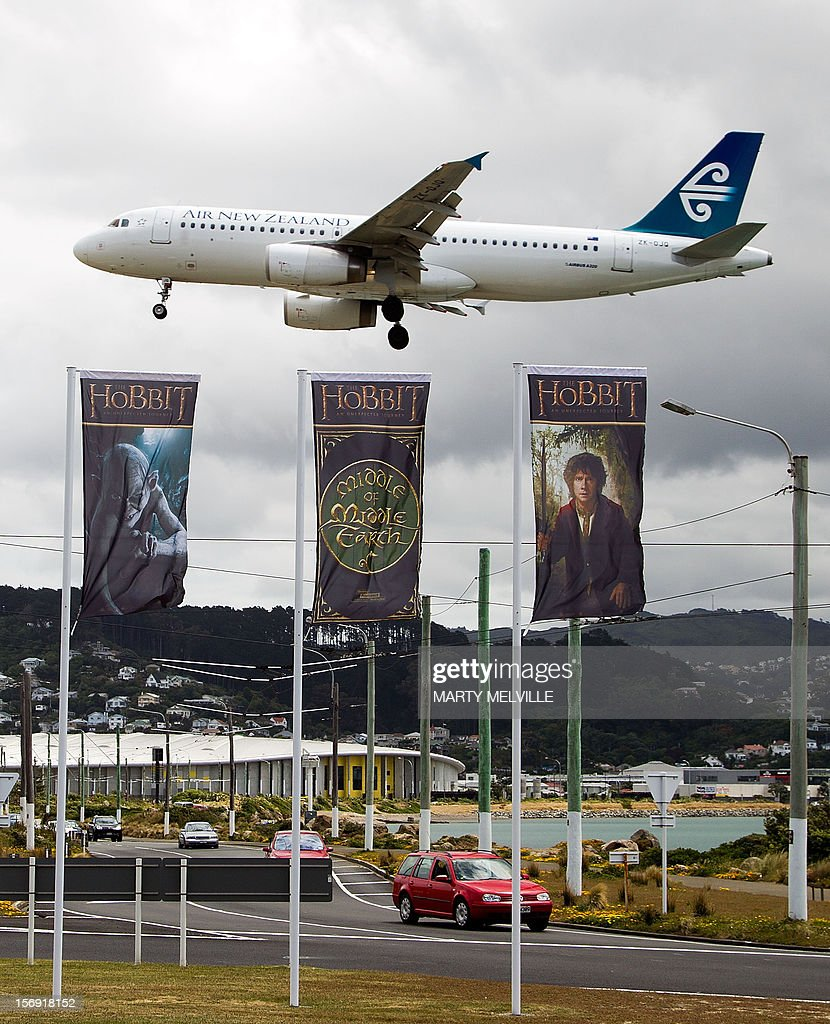 To go with 'Entertainment-NZealand-film-tourism-Hobbit,ADVANCER' by Neil Sands This picture taken on November 24th, 2012 shows flags advertising 'The Hobbit' movie fluttering as an Air New Zealand 737 comes in to land at Wellington airport in Wellington. Hobbit fever has seized New Zealand ahead and the capital is dotted with giant sculptures of key characters such as Gandalf the wizard atop the Embassy cinema and a bug-eyed Gollum greeting visitors at the airport.