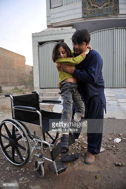 To go with feature 'Pakistanunrestamputees' by Khurram Shahzad Pakistan father Asim Khan helps his seven yearold disabled daughter Laiba into a...