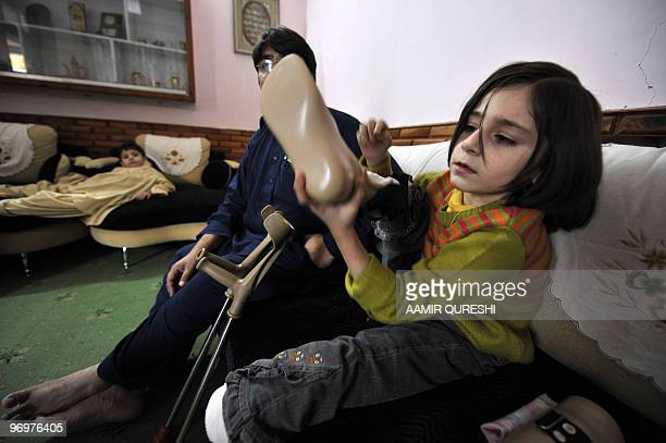 To go with feature 'Pakistanunrestamputees' by Khurram Shahzad Seven yearold disabled Pakistan girl Laiba adjusts her artificial foot as she sits on...