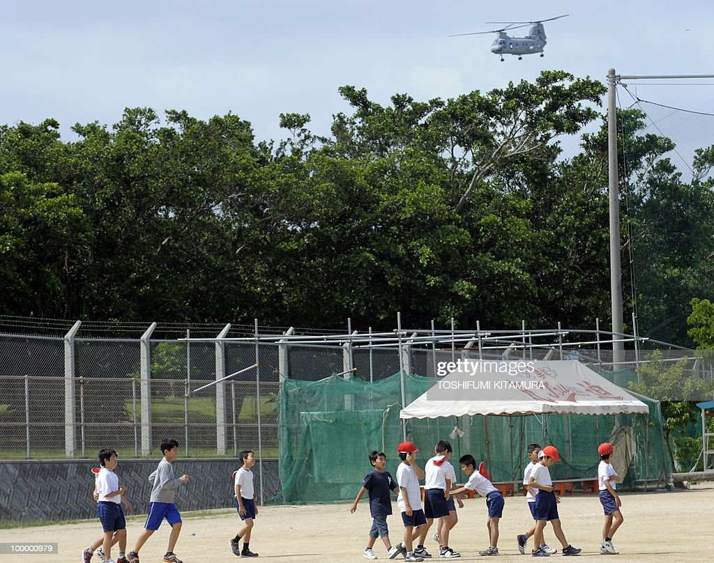To go with feature story Japan-US-military-diplomacy by Kyoko Hasegawa In a picture taken on April 26, 2010, a US CH-46E helicopter flies beside the primary school right next to the US Marine Corps Air Station Futenma in Ginowan, Okinawa prefecture. The deafening US military jets sometimes fly so low that the pilots' faces are visible to the people living around their airbase on the southern Japanese island of Okinawa. The base has been there since the palm-fringed island emerged from the battles of Word War II to become Japan's main US military staging area -- but many locals say they'll never get used to the ear-splitting noise.