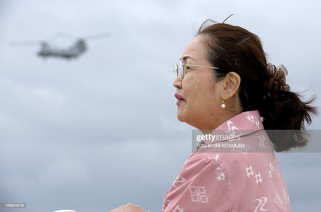 To go with feature story Japan-US-military-diplomacy by Kyoko Hasegawa In a picture taken on April 26, 2010, Harumi Chinen, the principal of Futenma primary school, which is located next to the US Marines Futenma Air Station, talks to journalists as a CH-46E helicopter flies in the background beside the school in Ginowan, Okinawa prefecture. The deafening US military jets sometimes fly so low that the pilots' faces are visible to the people living around their airbase on the southern Japanese island of Okinawa. The base has been there since the palm-fringed island emerged from the battles of Word War II to become Japan's main US military staging area -- but many locals say they'll never get used to the ear-splitting noise.