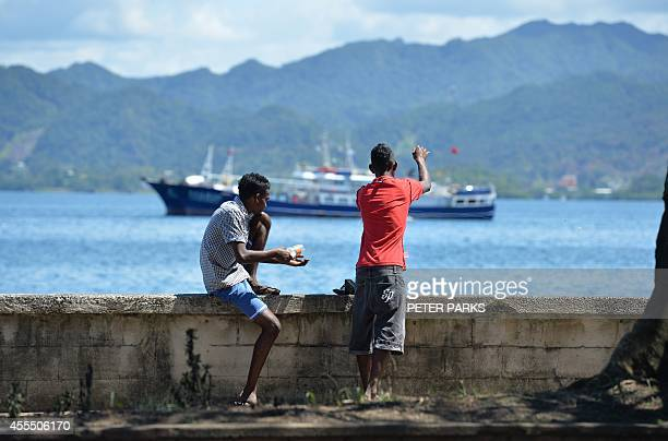 To go with FijivoteSCENE by Neil Sands This photo taken on September 15 2014 shows two men fishing as Fiji gets ready for the upcoming elections in...