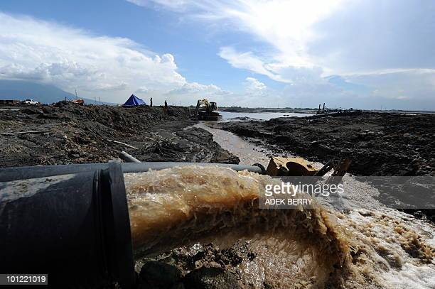 To go with focus story Indonesiaenvironmentmudanniversary by Adek Berry This picture taken on May 25 2010 shows a pipe discharging muddy water as...