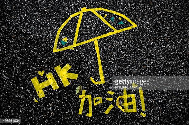 To go with Hong KongChinapoliticsdemocracyiconographyFOCUS by Annabel SYMINGTON A message of support made with yellow tape is seen on a road near the...