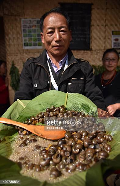 To go with 'IndiaFoodOrganicLifestyle' FEATURE by Etienne Fontaine In this photograph taken on November 7 an Indian Naga shows a dish made of...