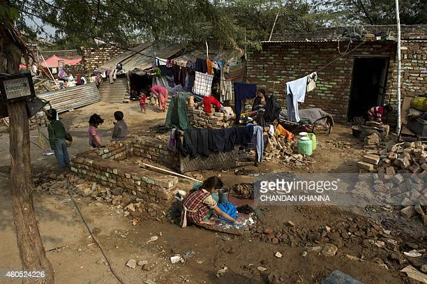 To go with IndiagovernmentplanningFOCUS by Trudy HARRIS and Bhuvan BAGGA This photo taken on December 12 2014 shows a resident cleaning her clothes...