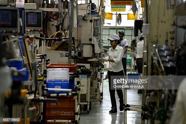 To go with 'IndiaPoliticsEconomyBusinessLabour' by Trudy Harris In this photograph taken on August 12 Indian workers manage machines at a factory of...