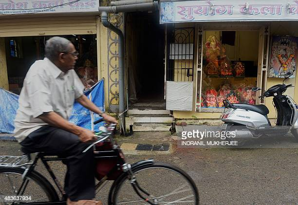 To go with 'IndiareligionfestivalGanesha' by Peter Hutchison In this photograph taken on August 6 an Indian cyclist rides past plaster idols of the...