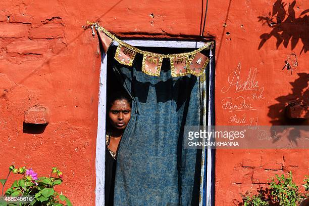 To go with IndiasocialhealthleprosyFEATURE by Abhaya SRIVASTAVA In this photograph taken on March 11 a leprosy patient looks out of her living...