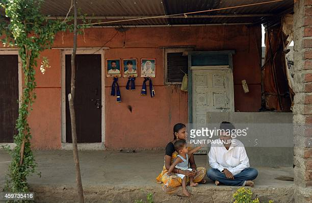 To go with Indiasocietycrimecaste by Rachel O An Indian family sits outside a house where flowergarlanded portraits of a dead family are seen on a...