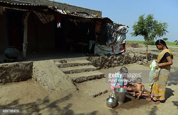 To go with Indiasocietycrimecaste by Rachel O Indian women bathe a child outside their house in Javkheda village in Ahmednagar district of India's...