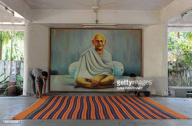 To go with IndiatourismGandhiFEATURE by Rajesh Joshi In this photograph taken on October 11 caretaker Bhim Bahdur spreads a carpet in the Prayer Hall...