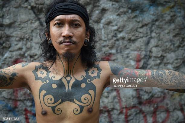To go with Indonesia culture tradition tattoo by Suryo Wibowo with Sam Reeves in Jakarta In this photograph taken on October 14 Ranu Khodir a...