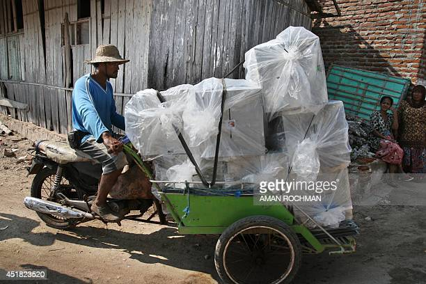 To go with Indonesiaelectionlogistics FOCUS by Arlina Arshad In this photograph taken on July 7 an Indonesian man transports on traditional becak...