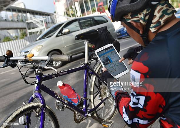 To go with IndonesiainterneturbanplanningFOCUS by Olivia Rondonuwu A cyclist checks for the traffic situation through the local's government new web...