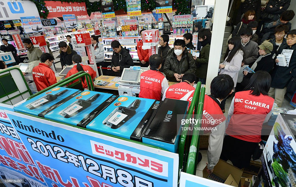 To go with 'Japan-US-game-entertainment-company-Nintendo,FOCUS' by Kyoko Hasegawa This picture taken on December 8, 2012 shows customers being attended to by cashiers (in red) as they purchase Japanese electronics titan Nintendo's new videogame console 'Wii U' at a shop in Tokyo. Nintendo is hoping its new Wii U console will catapult it back to pole position in the video game sector, but analysts are divided on whether the Japanese gaming titan can reboot its fading glory. AFP PHOTO/Toru YAMANAKA