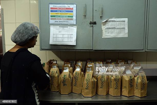 To go with 'LifestyleIndiafoodtechnologytiffin' FOCUS by PETER In this photograph taken on September 2 an Indian worker packs lunch boxes at an...