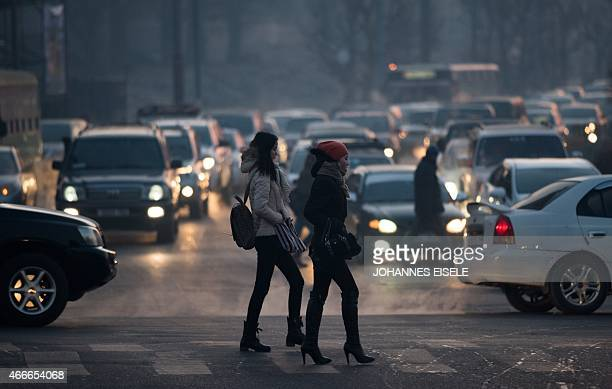To go with MongoliaclimateenvironmentweatherFEATURE by Kelly Olsen This photo taken on February 9 shows two women crossing a street in Ulan Bator...