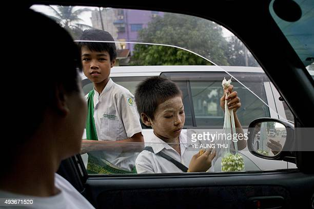 To go with MYANMARLABOURCHILDRENSOCIETY Feature by Marion THIBAUT In this picture taken on October 20 children sell flowers on a road on the...