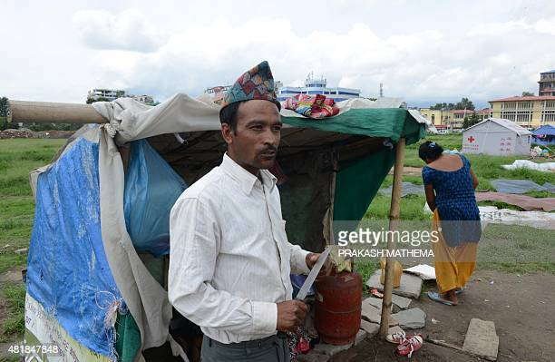 To go with ' NepalQuakeEconomyAid ' by Paavan Mathema In this photograph taken on July 23 Nepalese man Rabi Baral stands next to his tent set up at a...