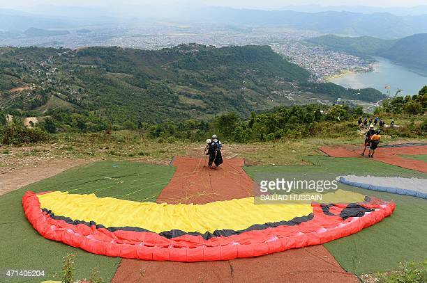 To go with 'NepalQuakeTouristPokhara' SCENE by Annie Banerji In this photograph taken on April 27 tourists take part in a paragliding session...
