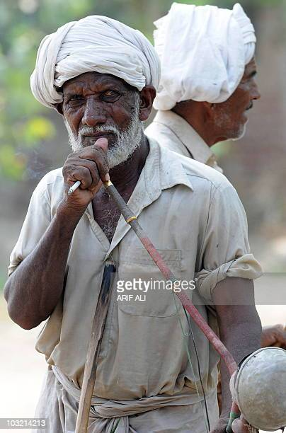 To go with PakistanIndiadiplomacywaterFOCUS by Waqar Hussain In this photograph taken on July 9 a Pakistani farmer smokes a cigarrette and tobacco...