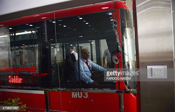 To go with PAKISTANTRANSPORTBUSPOLITICS by Masroor GILANI In this picture taken on June 1 a Pakistani Metrobus driver waits for officials and media...
