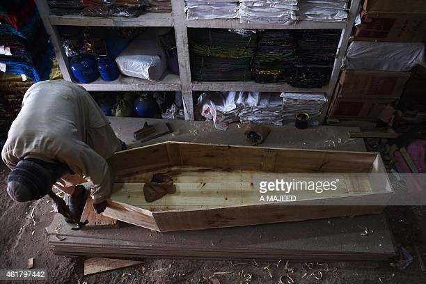 To go with PakistanunrestFOCUS by Khurram SHAHZAD This photograph taken on January 6 2015 shows a Pakistani carpenter making a coffin at a workshop...