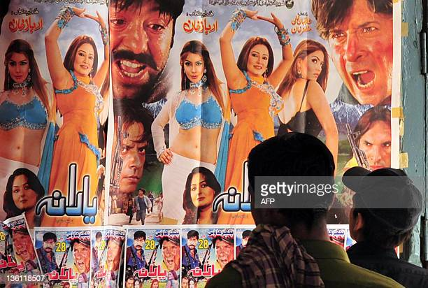 To go with 'PakistanunrestmusicFEATURE' by Sajjad Tarakzai In this photograph taken on October 29 2011 Pakistanis look at the film posters at a...