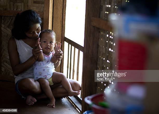 To go with PhilippinestyphoonpovertychildrenFEATURE by Karl Malakunas In this picture taken on October 17 Emily Sagalis holds her baby girl inside...